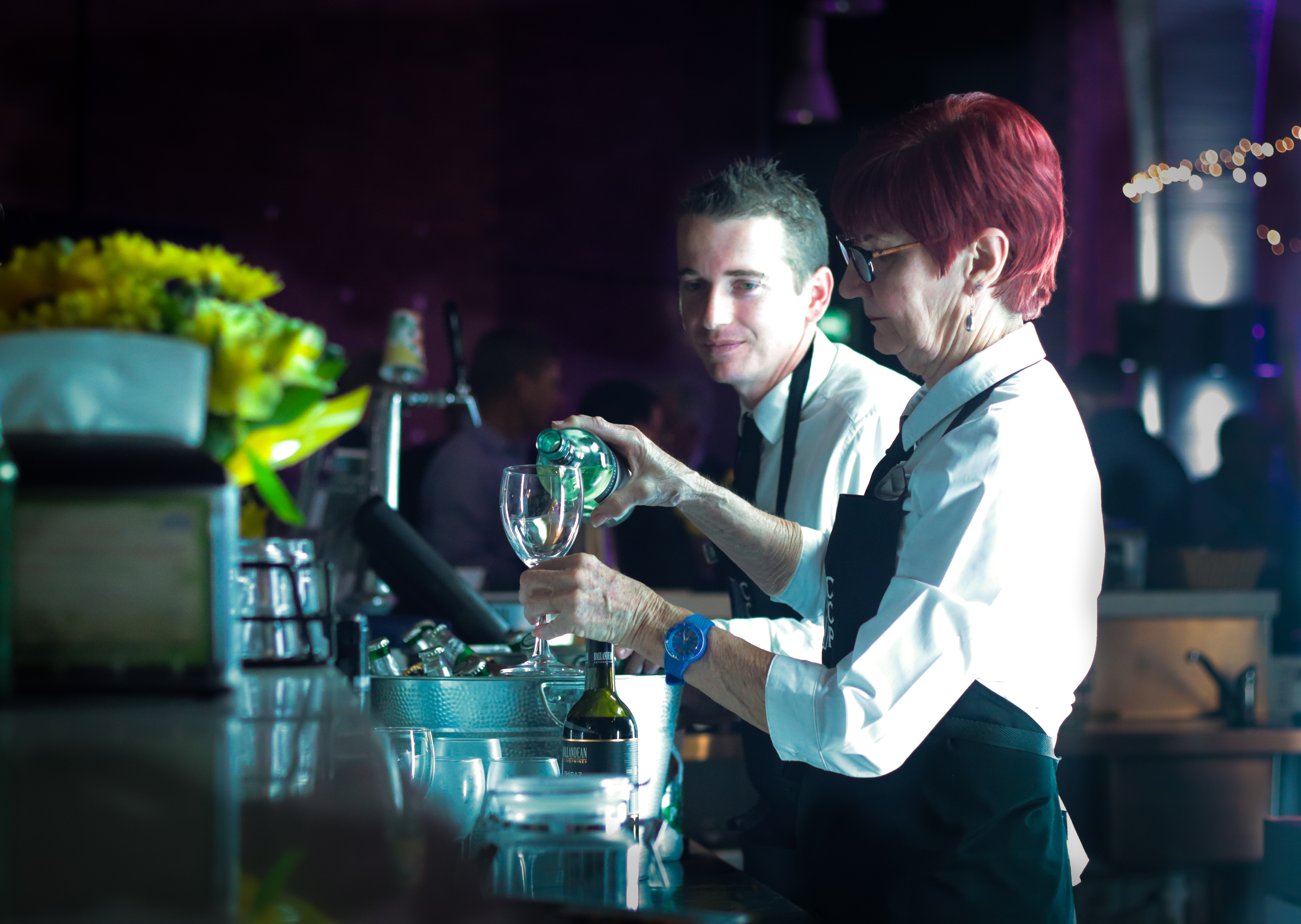Bar staff pouring wine. Lady with red hair and man with eyebrow ring