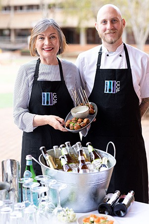 Woman and Man in aprons holding a plate of meatballs and a table with alcohol and glasses on it