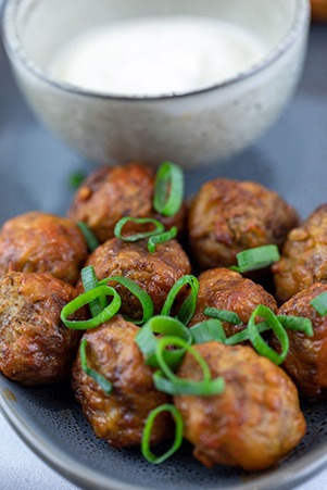 Plate of meatballs with dipping sauce and herbs