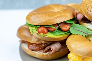 Close image of breakfast bagels with avocado and tomato filling and bacon and relish