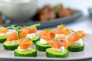 Side image of cucumber canapes and meatballs in the background