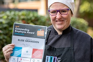 Image of woman in chefs hat holding certificate
