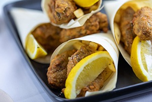 Fish and chip cups with slices of lemon