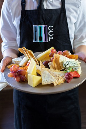Image of someone in a CCP apron holding a cheese platter