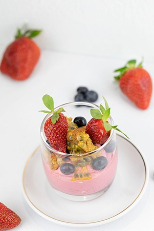 Top down image of a fruit cup with smoothie filling of fresh strawberries, blueberries and passionfruit