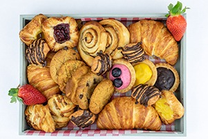 Top down of pastry box featuring danishes, chocolate croissants and tarts