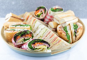 Plate of wraps, rolls and triangle sandwiches