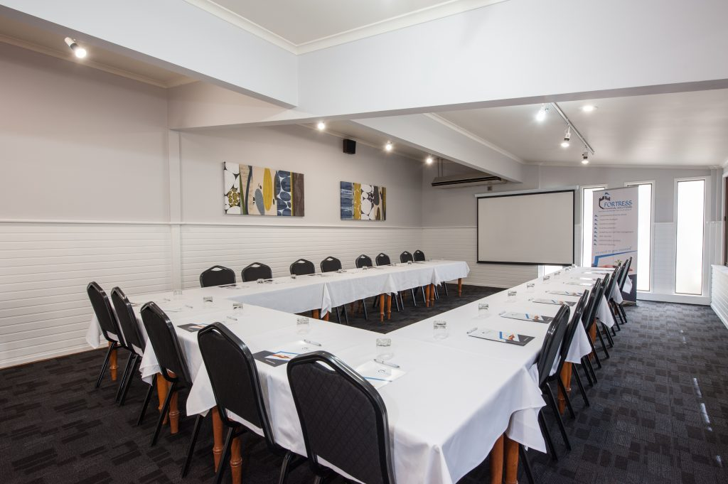 Bright room with a U shaped Table and chairs, set up for a meeting or training exercise.