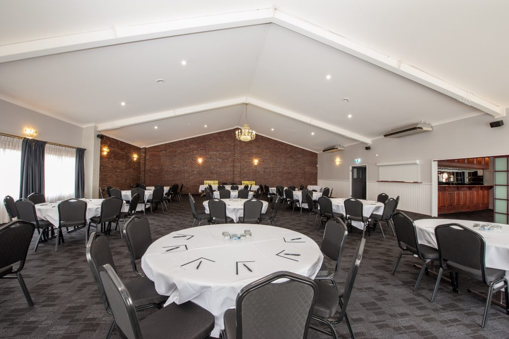 Function room setup with round tables, white table cloths and pens and notepads on the tables for functions