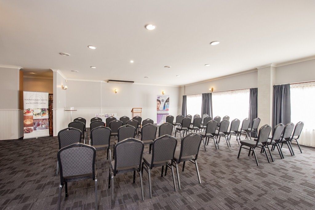 Bright room set up with 30 or so chairs for a speaking seminar