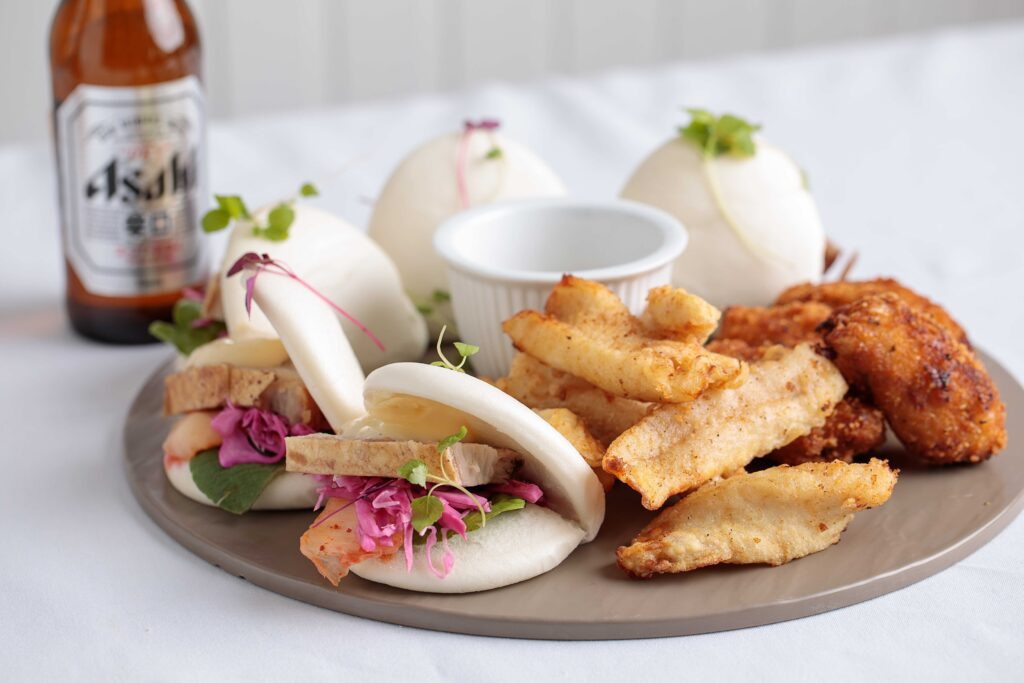 Platter with Bao Buns, chicken wings and an asahi beer